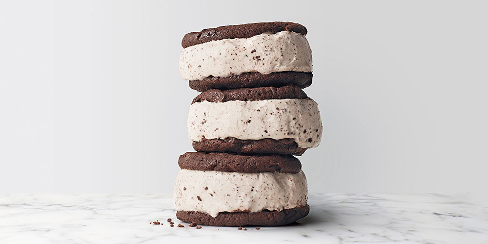 three cookie ice cream sandwiches with cookies and cream filling stacked on top of each other