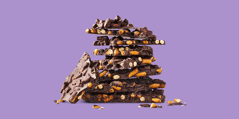 a stack of prezel-filled chocolate bark on a purple background